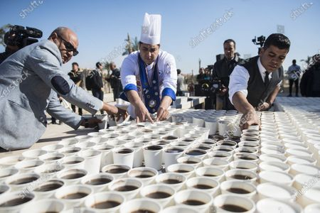 Helpers arrange cups with black coffee and milk coffee to create a mosaic depicting the ancient Egyptian pharaoh Tutankhamun's death mask outside the Grand Egyptian Museum (GEM), in Giza, Greater Cairo, Egypt, 28 December 2019. Media reports state that Guinness World Records organized the event to celebrate Egypt for 'breaking the world record with a picture of King Tutankhamun's mask' by using a total of 7,260 cups of coffee. The mosaic was meant as a 'symbol of love and greeting' according to an Egyptian Ministry of Tourism and Antiques statement. The museum is scheduled to present its full Tutankhamun collection by the end of 2020.