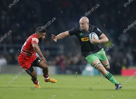 Tom Lawday of Harlequins fends away Kyle Eastmond of Leicester