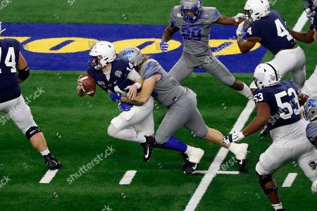 Stock Picture of Penn State quarterback Sean Clifford (14) is sacked by Memphis defensive lineman Jonathan Wilson (38) during the first half of the NCAA Cotton Bowl college football game in Arlington, Texas