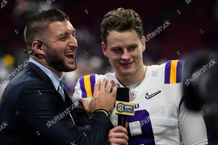 LSU quarterback Joe Burrow (9) speaks with former NFL player Tim Tebow after the Peach Bowl NCAA semifinal college football playoff game against Oklahoma, in Atlanta. LSU won 63-28
