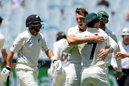 Australia's James Pattinson, center, hugs teammate Australia's Tim Paine, right, after capturing the wicket of New Zealand's Ross Taylor, left, during their cricket test match in Melbourne, Australia