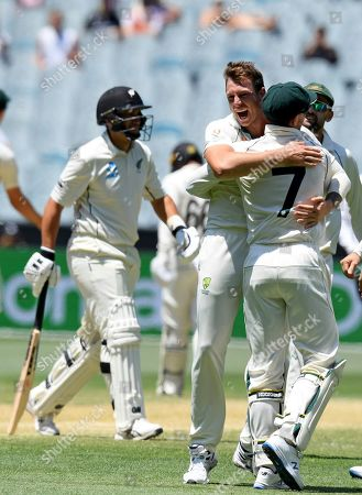 Australia's James Pattinson, second from right, hugs teammate Tim Paine after capturing the wicket of New Zealand's Ross Taylor, left, during their cricket test match in Melbourne, Australia