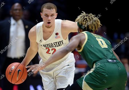 San Diego State guard Malachi Flynn (22) dribbles the ball while defended by Cal Poly guard Keith Smith (0) as Cal Poly coach John Smith, rear, watches during the second half of an NCAA college basketball game, in San Diego. San Diego won 73-57