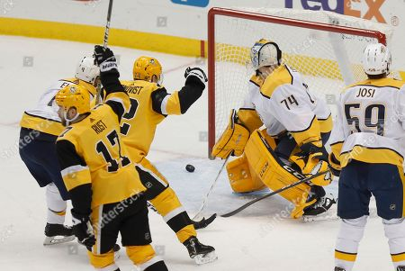 Pittsburgh Penguins' Bryan Rust (17) and Patric Hornqvist (72) celebrate a goal by Kris Letang on Nashville Predators goaltender Juuse Saros (74) during the first period of an NHL hockey game, in Pittsburgh