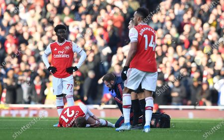 Arsenal's Calum Chambers (down) reacts in pain during the English Premier League soccer match between Arsenal FC and Chelsea FC held at the Emirates stadium in London, Britain, 29 December 2019.