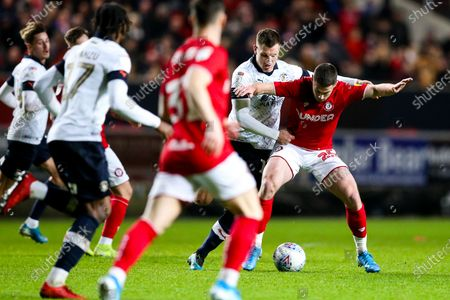 Tommy Rowe of Bristol City is tackled by James Collins of Luton Town