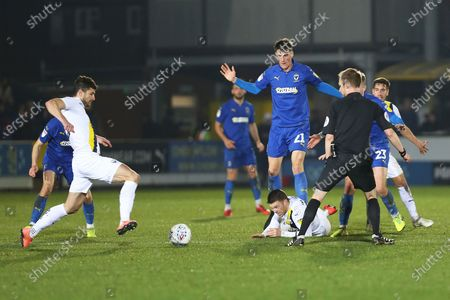 Ryan Delaney brings down Jamie Mackie during the EFL Sky Bet League 1 match between AFC Wimbledon and Oxford United at the Cherry Red Records Stadium, Kingston
