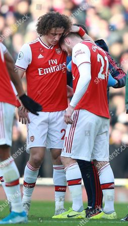 Arsenal's David Luiz, right, hugs his injured teammate Calum Chambers during the English Premier League soccer match between Arsenal and Chelsea, at the Emirates Stadium in London