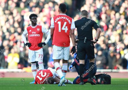 Arsenal's Calum Chambers lies injured on the pitch during the English Premier League soccer match between Arsenal and Chelsea, at the Emirates Stadium in London