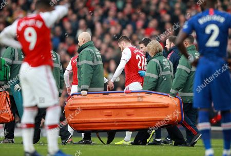Arsenal's Calum Chambers leaves the pitch after being injured during the English Premier League soccer match between Arsenal and Chelsea, at the Emirates Stadium in London