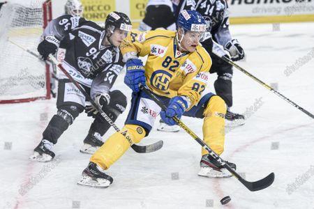 Stock Photo of Turku`s Henrik Larsson, left, against Davos' Harri Pesonen during the game between TPS Turku and HC Davos, at the 93rd Spengler Cup ice hockey tournament in Davos, Switzerland, Sunday, December 29, 2019.