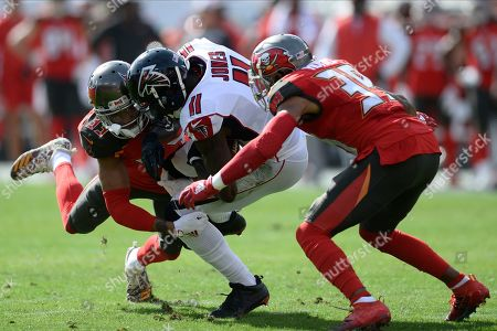 Tampa Bay Buccaneers cornerback Carlton Davis (33) and strong safety Andrew Adams (39) take down Atlanta Falcons wide receiver Julio Jones (11) during the first half of an NFL football game, in Tampa, Fla