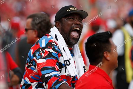 Former Tampa Bay Buccaneers' Warren Sapp laugh during the first half of an NFL football game between the Buccaneers and the Atlanta Falcons, in Tampa, Fla