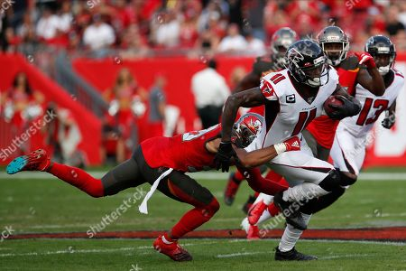 Atlanta Falcons wide receiver Julio Jones (11) slips a tackle by Tampa Bay Buccaneers strong safety Andrew Adams (39) during the first half of an NFL football game, in Tampa, Fla