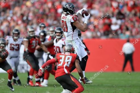 Atlanta Falcons tight end Austin Hooper (81) makes a catch in front of Tampa Bay Buccaneers strong safety Andrew Adams (39) during the second half of an NFL football game, in Tampa, Fla