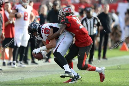 Atlanta Falcons tight end Austin Hooper (81) is stopped by Tampa Bay Buccaneers strong safety Andrew Adams (39) during the second half of an NFL football game, in Tampa, Fla