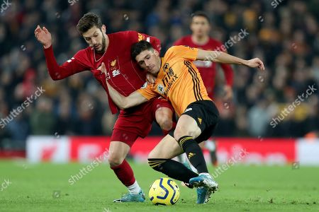Liverpool's Adam Lallana fights for the ball with Wolverhampton Wanderers' Ruben Vinagre, right, during the English Premier League soccer match between Liverpool and Wolverhampton Wanderers at Anfield Stadium, Liverpool, England