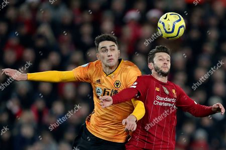 Wolverhampton Wanderers' Max Kilman, left, vies for the ball with Liverpool's Adam Lallana during the English Premier League soccer match between Liverpool and Wolverhampton Wanderers at Anfield Stadium, Liverpool, England