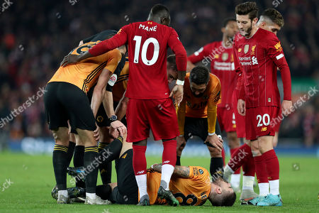 Wolverhampton Wanderers' Ruben Neves lies on the ground following a clash with Liverpool's Adam Lallana, right, during the English Premier League soccer match between Liverpool and Wolverhampton Wanderers at Anfield Stadium, Liverpool, England