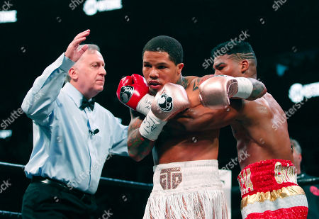 Yuriorkis Gamboa, right, wraps up opponent Gervonta Davis, center, as referee Jack Reiss breaks them up in the ninth round as they fight in the WBA lightweight boxing bout n Atlanta
