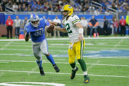 Stock Image of Green Bay Packers quarterback Aaron Rodgers (12) is rushed by Detroit Lions defensive end Trey Flowers (90), during the second half of an NFL football game, in Detroit