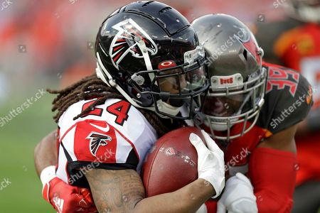 Atlanta Falcons running back Devonta Freeman (24) is stopped by Tampa Bay Buccaneers strong safety Andrew Adams (39) on a run during the first half of an NFL football game, in Tampa, Fla