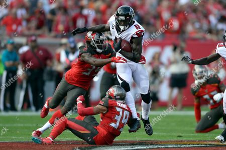 Tampa Bay Buccaneers defensive back Jamel Dean (35) and strong safety Andrew Adams (39) team up to stop Atlanta Falcons wide receiver Julio Jones (11) after a catch during the first half of an NFL football game, in Tampa, Fla