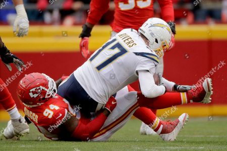 Stock Photo of Terrell Suggs, Philip Rivers. Kansas City Chiefs defensive end Terrell Suggs (94) sacks Los Angeles Chargers quarterback Philip Rivers (17) during the second half of an NFL football game in Kansas City, Mo