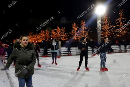 People skate in an ice skating rink decorated for Christmas at the Stavros Niarchos Foundation Cultural Centre in Athens, Greece, 29 December 2019.