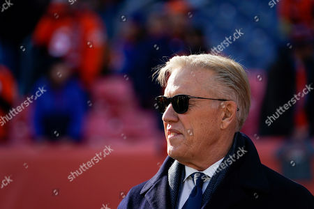 Denver Broncos general manager John Elway looks on as the team warms up before an NFL football game against the Oakland Raiders, in Denver