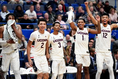 Connecticut's Josh Carlton (25), James Bouknight (2), Alterique Gilbert (3), Christian Vital (1), and Tyler Polley (12) cheer for a bench player in the closing seconds of their game against the New Jersey Institute of Technology during an NCAA college basketball game, in Hartford, Conn
