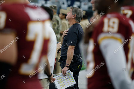 Washington Redskins head coach Bill Callahan, center, stands for the national anthem before an NFL football game against the Dallas Cowboys in Arlington, Texas