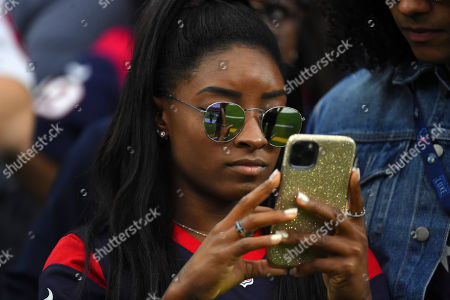 Olympic gymnast Simone Biles waits to lead the Houston Texans onto the field as the home field advantage captain before an NFL football game against the Tennessee Titans, in Houston
