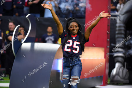 Olympic gymnast Simone Biles leads the Houston Texans out to the field as the homefield advantage captain before an NFL football game against the Tennessee Titans, in Houston