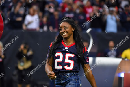 Olympic gymnast Simone Biles leads the Houston Texans onto the field before an NFL football game against the Tennessee Titans, in Houston