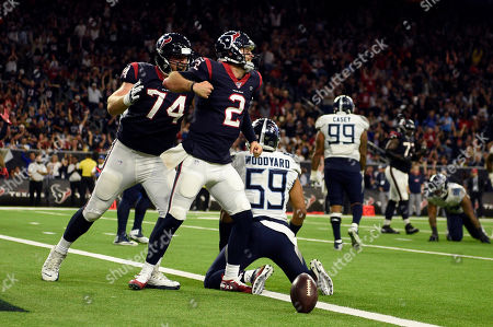 Stock Image of Houston Texans quarterback AJ McCarron (2) celebrates after scoring a touchdown as offensive guard Max Scharping (74) joins him while Tennessee Titans inside linebacker Wesley Woodyard (59) kneels at the goal line during the second half of an NFL football game, in Houston