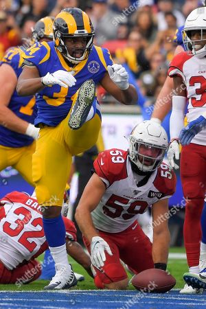 Los Angeles Rams running back Malcolm Brown celebrates after scoring as Arizona Cardinals linebacker Joe Walker looks on during first half of an NFL football game, in Los Angeles