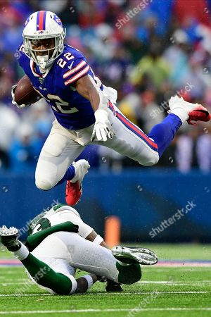 Buffalo Bills running back T.J. Yeldon (22) hurdles New York Jets strong safety Jamal Adams (33) during the second half of an NFL football game in Orchard Park, N.Y