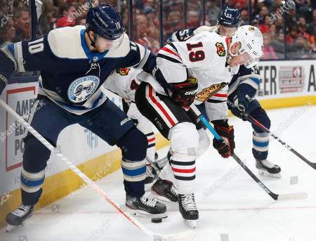 Chicago Blackhawks forward Jonathan Toews, right, works in front of Columbus Blue Jackets forward Alexander Wennberg, of Sweden, during the first period of an NHL hockey game in Columbus, Ohio
