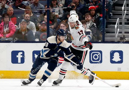 Columbus Blue Jackets forward Alexander Wennberg, left, of Sweden, controls the puck in front of Chicago Blackhawks forward Dylan Strome during the second period of an NHL hockey game in Columbus, Ohio