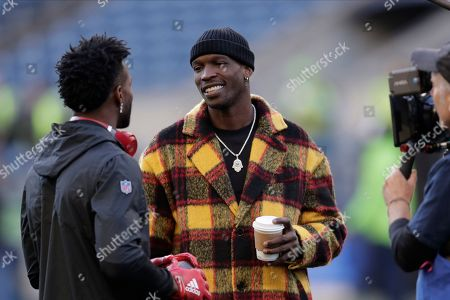 Stock Photo of Former NFL player Chad Ochocinco talks with players on the field before an NFL football game between the Seattle Seahawks and the San Francisco 49ers an NFL football game, in Seattle