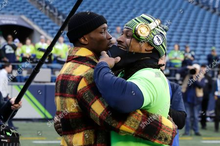 Seattle Seahawks' Marshawn Lynch, right, embraces former NFL player Chad Ochocinco before an NFL football game against the San Francisco 49ers an NFL football game, in Seattle