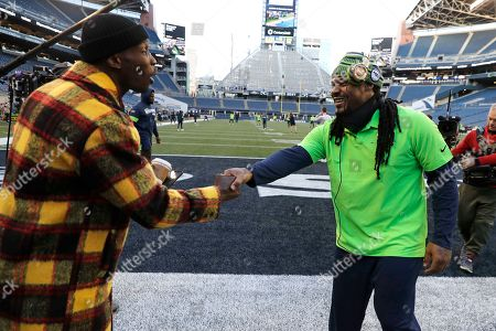 Stock Image of Seattle Seahawks' Marshawn Lynch, right, shakes hands with former NFL player Chad Ochocinco before an NFL football game against the San Francisco 49ers an NFL football game, in Seattle