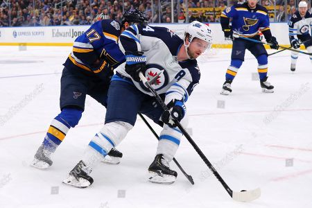 Winnipeg Jets defenseman Josh Morrissey (44) controls the puck against the St. Louis Blues during the third period of an NHL hockey game in St. Louis