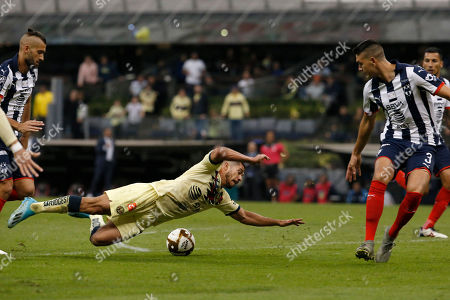 America's Henry Martin, center, falls on the pitch between Monterrey's Nicolas Sanchez, left, and Maximiliano Meza during their Mexican soccer league second-leg final match at Azteca stadium in Mexico City