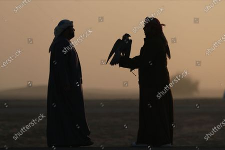 A man (R) stands with his gyrfalcon during the Fazza Championship for Falconry in Dubai, United Arab Emirates (UAE), 30 December 2019. The Fazza Championship for Falconry is sponsored by Dubai's Crown Prince Sheikh Hamdan bin Mohammed bin Rashid Al Maktoum. Falconry, locally known as 'kanas' is an integral part of the heritage of the UAE. The falconry tournaments run until the end of March 2020.