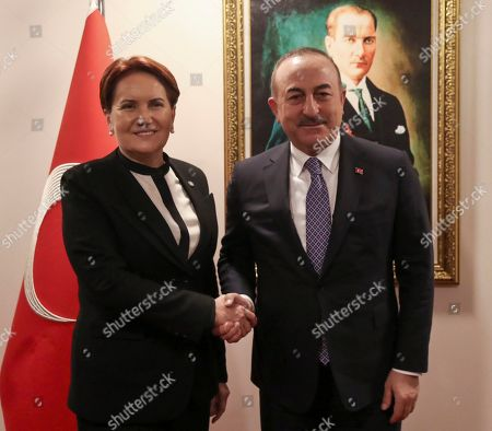 """Mevlut Cavusoglu, Meral Aksener. Turkey's Foreign Minister Mevlut Cavusoglu, right, and Meral Aksener, the leader of the nationalist opposition IYI """"Good"""" Party, shake hands before a meeting, in Ankara, Turkey, . Cavusoglu is seeking support for the government's plans to deploy Turkish troops to Libya"""