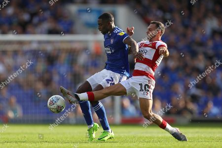Kane Vincent-Young of Ipswich Town holds off Jon Taylor of Doncaster Rovers