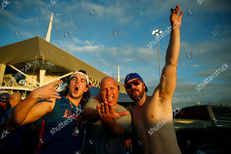 Florida Gator fans, Daniel Halfaker, 22, of Miami, left, Jacob Meyer, 37, of Cape Coral, Fla., center, and Race Land, 35, right, of South Carolina, tailgate before the Orange Bowl NCAA college football game between Florida and Virginia, in Miami Gardens, Fla