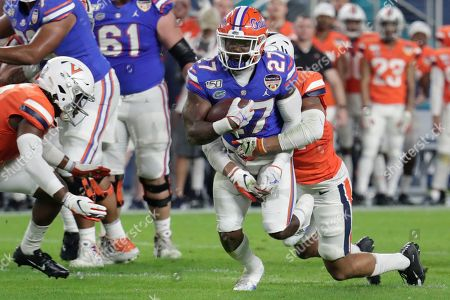 Stock Image of Florida running back Dameon Pierce (27) runs as Virginia linebacker Noah Taylor defends during the first half of the Orange Bowl NCAA college football game, in Miami Gardens, Fla